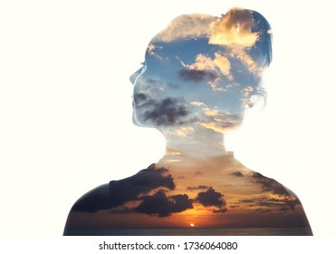 Double exposure portrait of a woman in contemplation at sunset time