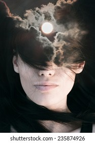 Double exposure portrait of young woman combined with photograph of sun among clouds