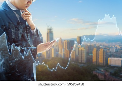 Double exposure of professional businessman connect internet in smart phone and city of business centre in blue cool tone with financial graph, Business , finance , trading and banking concept