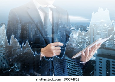 Double exposure of professional businessman hold and analyze tablet with cityscape and financial / trading graph in Business trading and technology concept