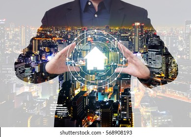 Double exposure property management concept - businessman show house symbol between hands with city overlay