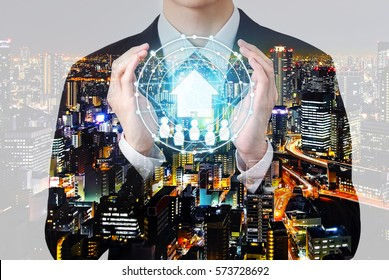 Double exposure property management concept - businessman hold house symbol in hands with city overlay
