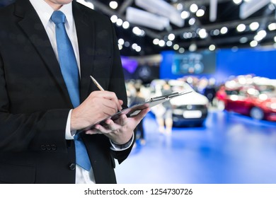 Double exposure of saleman hands holding trade booking with blurred background of new car displayed in showroom dealer, buying new car.