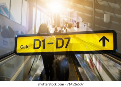 Double exposure of sign at airport with gate arrow for departing flights,