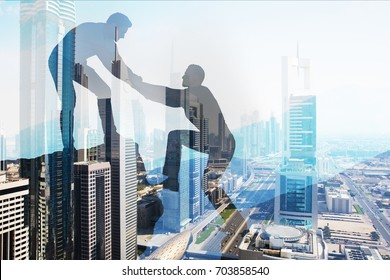 Double exposure of silhouette businessman helping colleague to climb over cityscape background