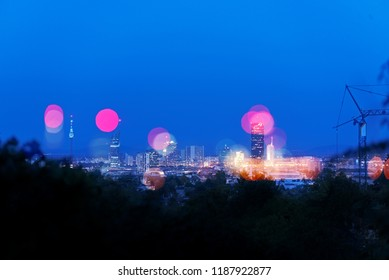 Double exposure of skyscrapers of Vienna Donaucity, overlaid with its defocused lights, on a dusky evening with clear blue sky.