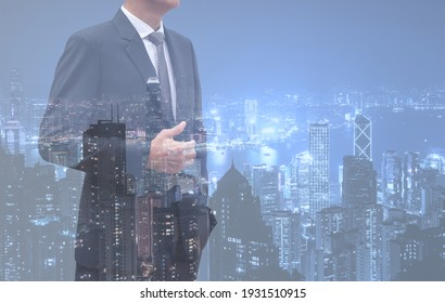 Double exposure of smart businessman in black suit and landscape buildings with night light in the city, copy space for business finance background