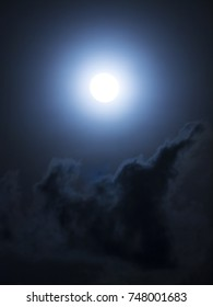 A double exposure of a soft focus full moon high in the sky as dark clouds pass by, Thailand