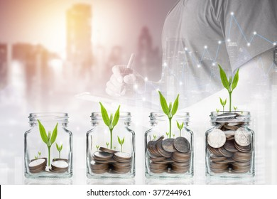 Double exposure of success businessman using digital tablet with coins with seed in clear bottle,Business investment growth concept,saving concept on city landscape background