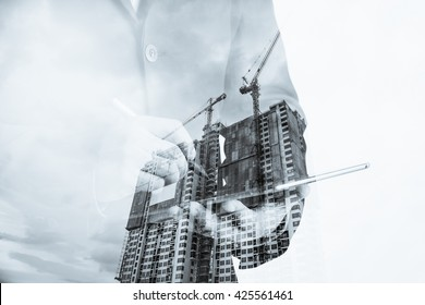 Double exposure of success businessman using digital tablet with Construction site with crane and building,business background