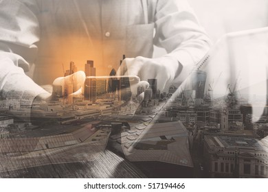 Double exposure of success businessman using  phone,digital tablet docking smart keyboard  with London building,city,omnichannel