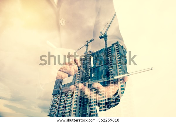 Double exposure of success businessman using digital tablet with Construction site with crane and building
