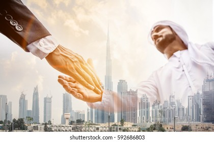 Double exposure of two business men over Dubai skyline building background. Arabian and western man handshaking concept