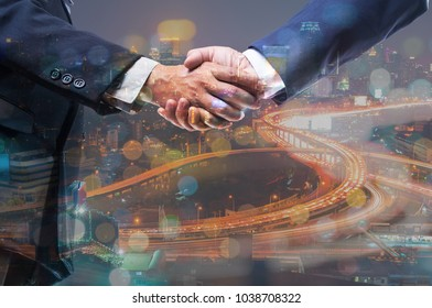 Double Exposure of Two Businessmen Shaking hand with Modern City Building Scene or Cityscape with Expressway or Highway at Twilight as Business Matching or Meeting Partner Concept.