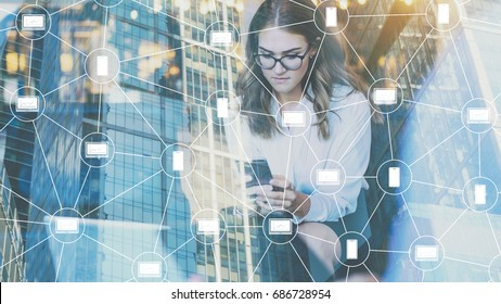 Double exposure. Virtual icons, blockchain technology. Young businesswoman in glasses sitting in office and using smartphone.Hipster girl working, planning,blogging online.Online education, marketing.