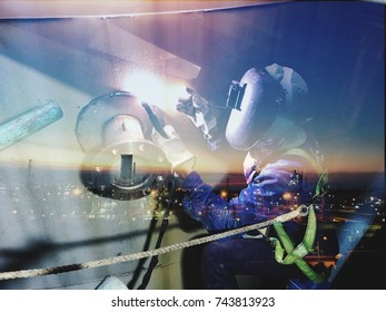Double exposure welding worker welding piping with oil and gas refinery plant of petroleum or petrochemical industry production in background