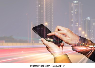 Double exposure of woman hand hold and touch screen smartphone, cellphone, light trails on the street and urban in the night as business and high speed of communication concept.