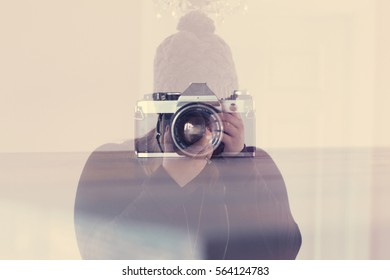 Double Exposure of Woman Holding Digital Camera with Vintage Film Camera Overlayed
