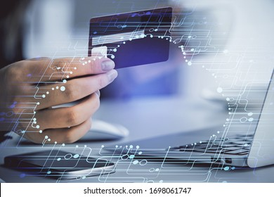 Double exposure of woman on-line shopping holding a credit card and data theme hologram drawing. E-commerce concept.