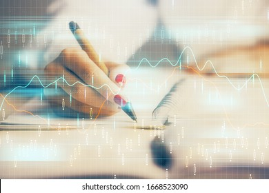 Double exposure of woman's hands making notes with forex graph hologram. Concept stock market analysis.