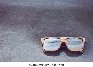 double exposure of wooden sunglasses and beach with concrete glossy background
