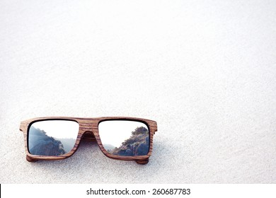 double exposure of wooden sunglasses and mountains with white sand background