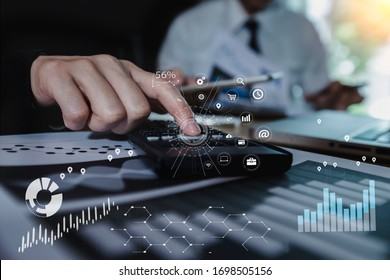 Double exposure of working team meeting concept, businessman using calculator with smart phone and laptop and digital tablet computer at the office.