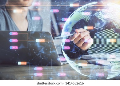 Double exposure of world map hologram with man working on computer on background. Concept of worldwideweb.