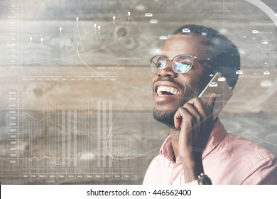 Double exposure. Worldwide communications concept. Happy and cheerful young black man talking to his partner using modern smart phone, laughing and looking up at futuristic screen interface with icons