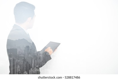 Double exposure of Young Asian businessmen and a city using touchpad for teaching and training.