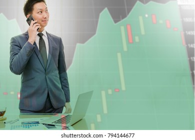 Double exposure of young businessman talking on the phone happily with a technical graph of the stock profits in background.