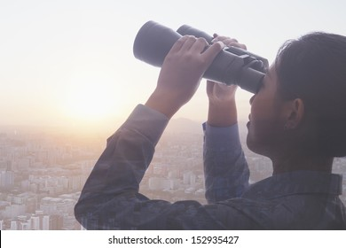 Double exposure of young businesswoman holding binoculars over cityscape of Beijing