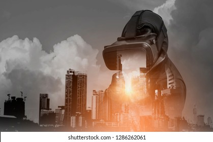 Double exposure-Men enjoy boxing games with VR goggles, headgear and 3D simulation through glasses Virtual reality, with city landscape background,concept to experience virtual technology of future