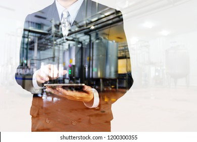 Double Expsure of Businessman in suit use Wireless Digital Tablet Device with Blur Background of Factory as Industrial Business concept.