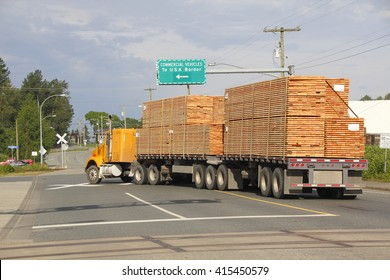 A double flatbed truck navigates to the US border delivering Canadian wood products.