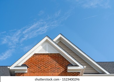 Double gable with beige horizontal vinyl lap and red brick facade siding,   with triangle shape white attic vent  on a pitched roof attic at an American single family home neighborhood USA