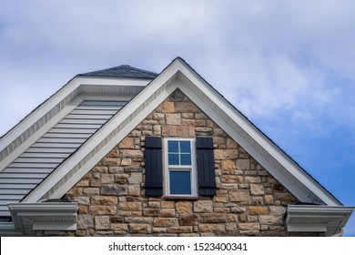 Double gable with colored stone facade siding, double hung window with white frame, vinyl shutters on a pitched roof attic at a luxury American single family home neighborhood USA