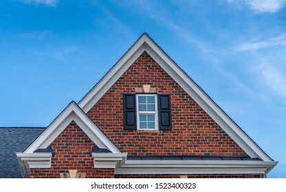 Double gable with red brick facade siding, double hung window with white frame, vinyl shutters on a pitched roof attic at a luxury American single family home neighborhood USA