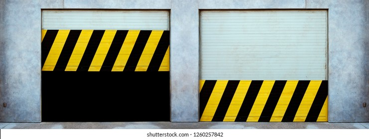 Double garage shutter doors with black and yellow caution stripes.