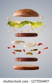 Double hamburger with lettuce onion and pickles floating with ingredients broken down in parts on gray gradient isolated background. Front view. Vertical composition.