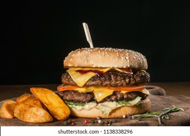 double hamburger with potatoes on a black background