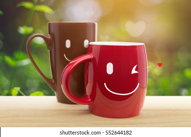 Double happy mugs in the garden, Two cup of coffee with a happy smile, Good day, Good morning or Have a happy day concept