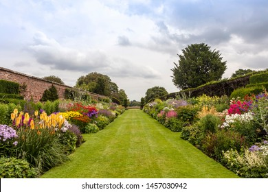 Double herbaceous borders with profusion of flowering perennial plants in the height of summer.
