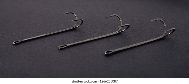 double hooks for fishing of various sizes on a black background close-up