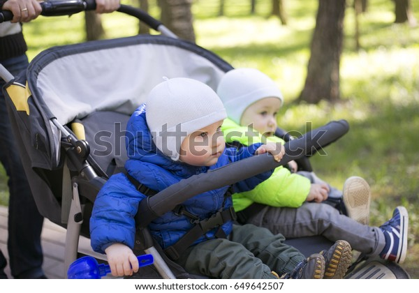 double jogging stroller with two kids, baby boy walking in a beautiful village