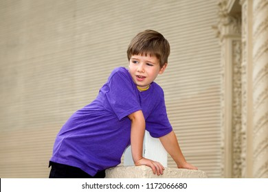 A double jointed little boy with hypermobility of the elbow leans forward with his weight on his arm.  He is waring a yellow necklace and stands in front of corrugated metal. Lots of copy space.