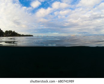 Double landscape with sea and sky. Above and below waterline in tropical seashore. Dark seawater and sunny sky. Sunset on beach. Exotic island shore view. Marine background. Tropical seaside vacation