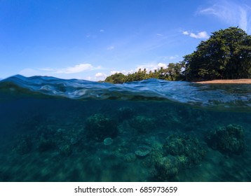 Double landscape with sea and sky. Sea panorama split photo. Undersea view of coral. Tropical island beach. Above and below sea waterline. Blue seawater with coral reef. Exotic island seaside vacation