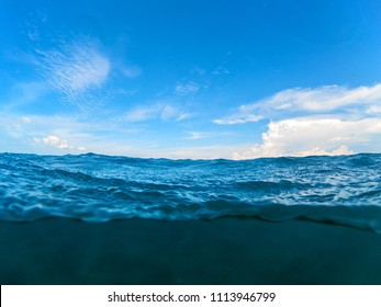 Double landscape with sea and sky. Seascape split photo. Double seaview with clouds on blue sky. Above and below waterline. Sea water border. Warm tropic seashore  banner template with text place