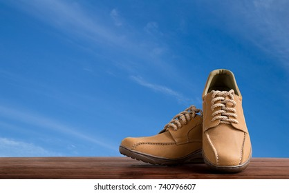 Double leather shoes for man on wooden table with blue Sky background.